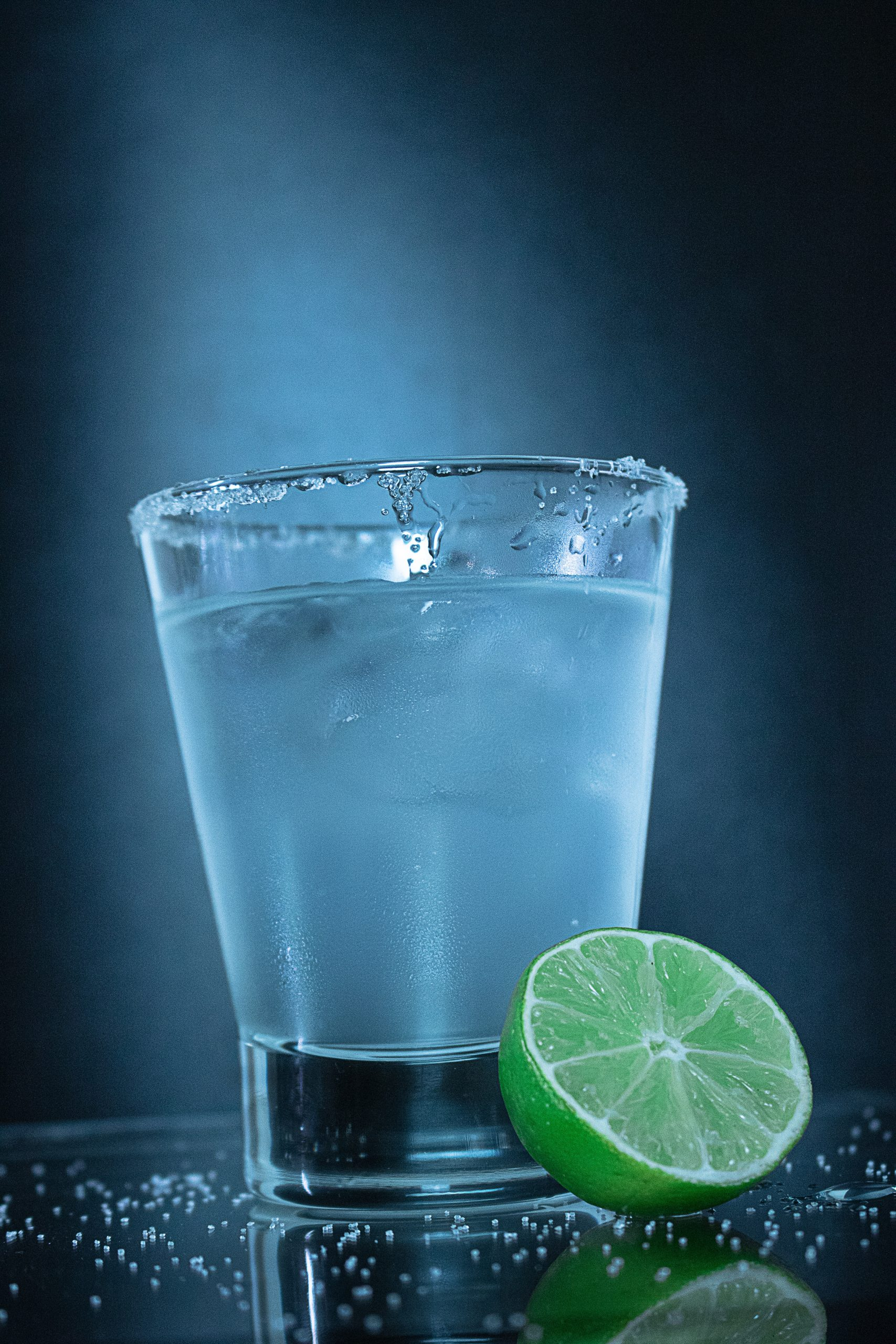 clear drinking glass beside green lime